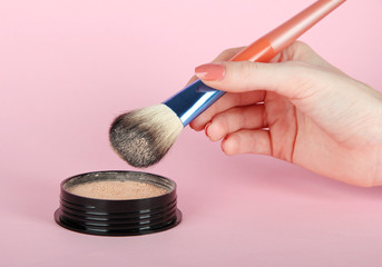 Powder and brush in hand on pink background