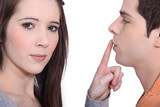 Woman putting her finger on a man's lips