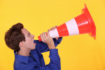 Man shouting through traffic cone