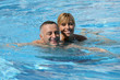 Happy couple swimming together in pool