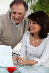 Middle-aged couple doing some on-line shopping