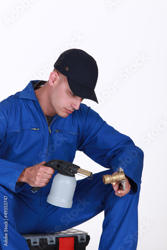 Plumber using blow torch on brass pipe