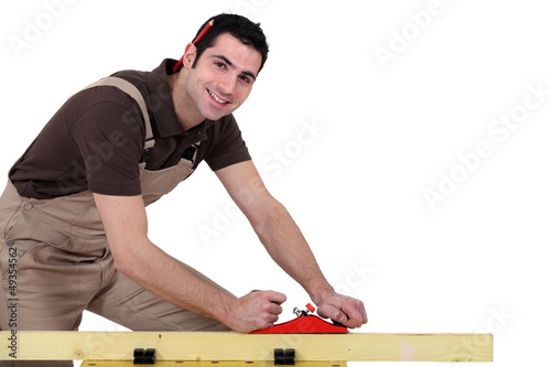Man with a sander and a pen