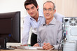 Man helping granddad with computer