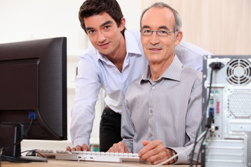 Man helping granddad with computer