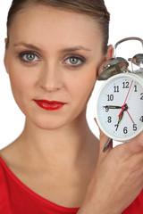 Blond woman displaying alarm clock