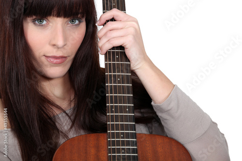 Brunette holding acoustic guitar