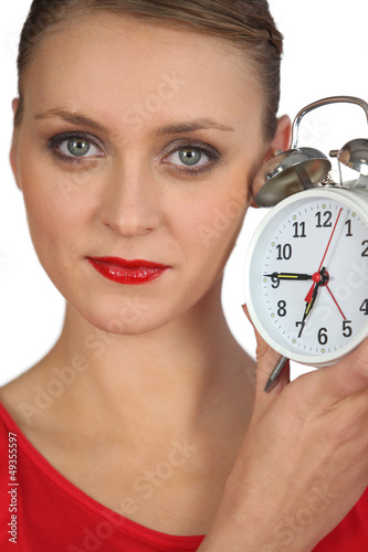 Blond woman displaying alarm clock