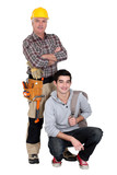 Experienced tradesman posing with his new apprentice