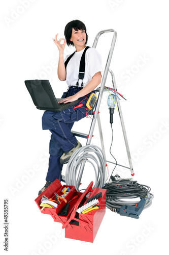 Female electrician with a laptop