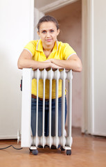 smiling woman  near warm radiator