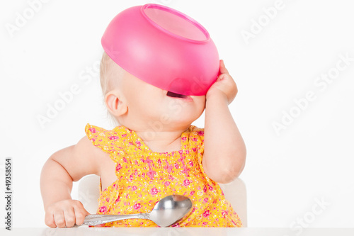 Little girl with a pink plate, on a gray background