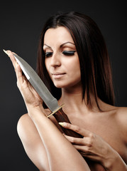 Close-up view of passionate Arab woman holding a knife in her ha