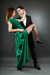 Pasionate young couple dancing tango over grey background