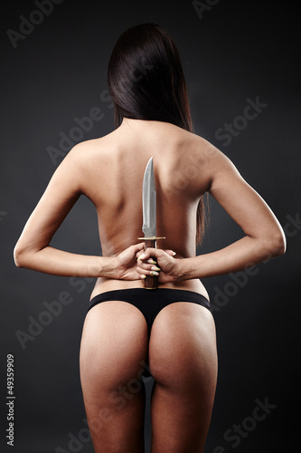 Sexy brunette woman hiding a knife behind her back
