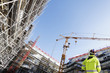 Leinwanddruck Bild - surveyor with instrument inside building-site, super wide view