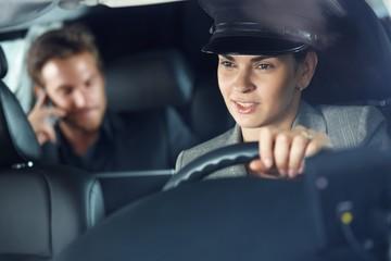 Female chauffeur driving a limousine