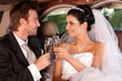 Bride and groom clinking glasses