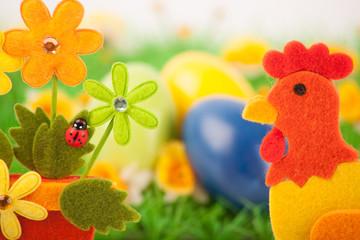 Bunte Eier auf Wiese vor Blumendeko mit Hahn