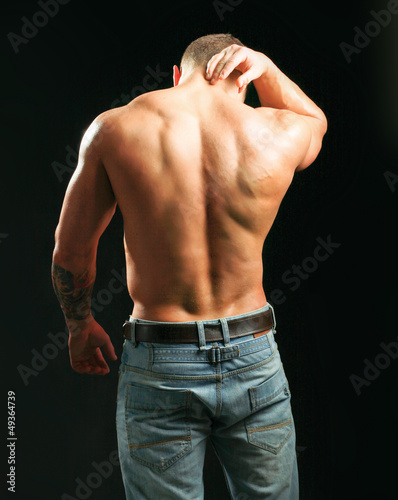 Muscular man with back neck ache isolated