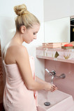 Woman the blonde in a pink towel washes hands