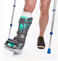 Man with a broken leg with Crutches on a white background