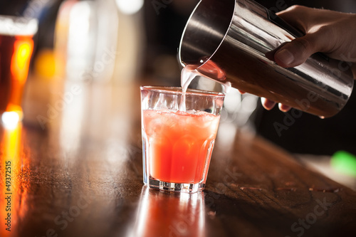 Barman serving a cocktail from a shaker