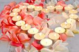 Brennendes Herz aus Kerzen mit Rosenblütenblättern