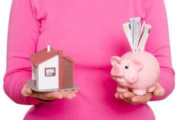 Haus und Sparschwein auf einer Hand