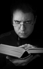 man with book looking at camera