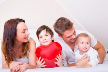 glückliche familie zuhause im bett