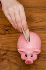 Hand steckt 50 Euro in ein Sparschwein