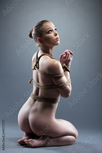 Nude young woman with shibari sitting on floor
