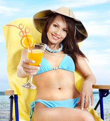 Girl in bikini drinking orange juice.
