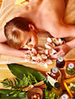 Woman getting herbal ball massage treatments .