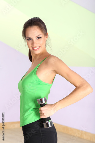 Young woman doing fitness exercises with dumbbell at gymnasium