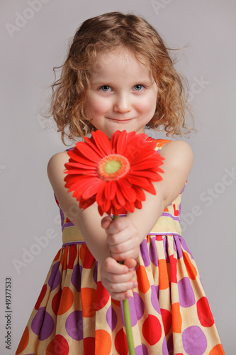Happy little girl gives a flower to someone