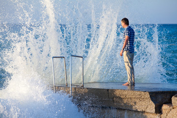 Man on the pier in big wave with splashes