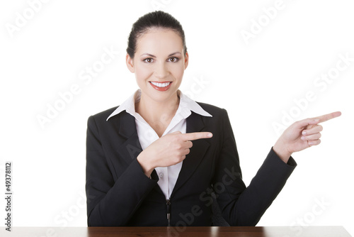 Businesswoman at the desk pointing to empty copy space