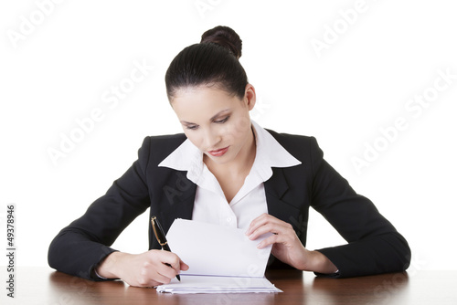 Businesswoman sitting at desk and writing.