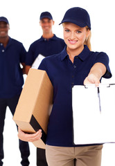 pretty delivery woman with parcel and receiving paper