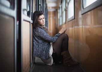 Femme seule adossée dans les couloirs d'un train