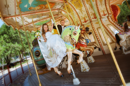 beautiful bride and groom riding a carousel