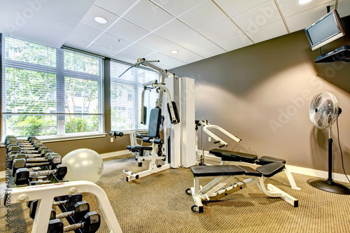 Gym in apartment building with brown wall and TV.