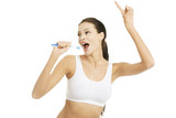Happy pretty woman singing to tooth brush