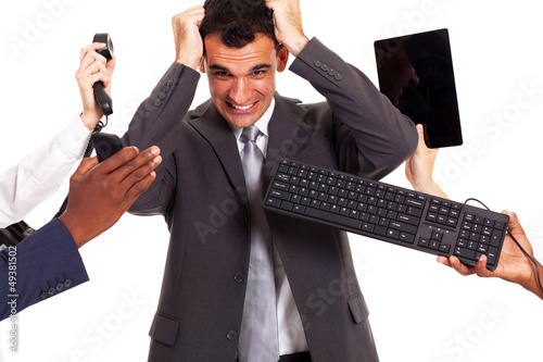 frustrated businessman around by multiple office tools