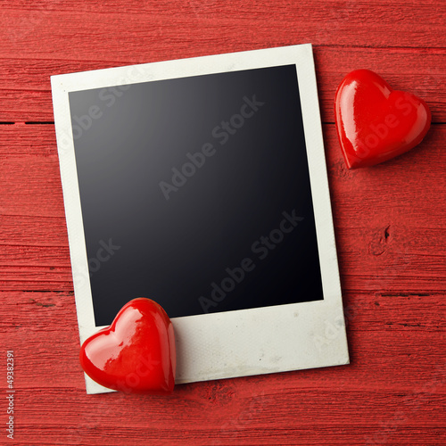 Blank photo and small red hearts on grunge background.