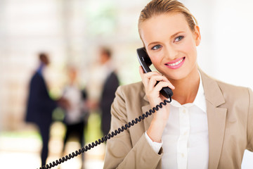 pretty businesswoman talking on landline phone in office