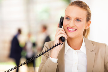happy female office worker talking on landline phone