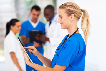 attractive young medical nurse using tablet computer